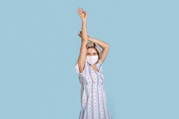 Modische frau mit blonden haaren, die ein sommerkleid und eine medizinische maske trägt, posiert auf einem blauen stu...