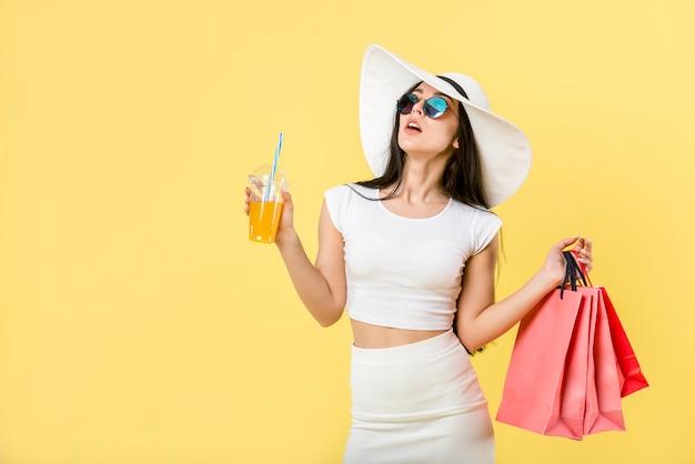 Modische frau mit cocktail und einkaufstaschen