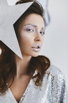 Modische frau mit hellem make-up im trendigen outfit, das mit neujahrsdekoration aufwirft