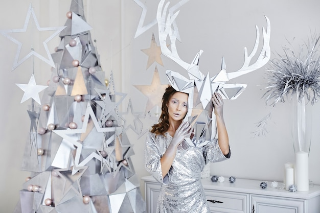 Modische frau mit hellem make-up im trendigen outfit, das mit weihnachtsdekoration aufwirft