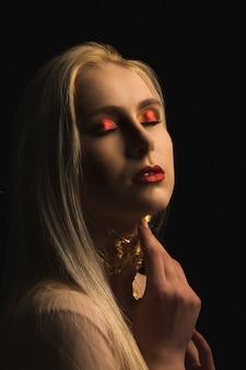 Modische frau mit hellem make-up und goldfolie am hals