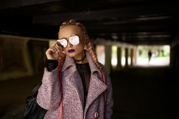 Modische frau mit rosa zöpfen in einem rosa mantel mit runden gläsern posiert auf der straße in einem tunnel
