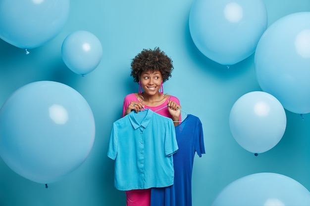 Modische frau wählt zwischen zwei kleidungsstücken, hält blaues kleid und hemd auf kleiderbügeln, denkt, was besser zu tragen ist, will elegant aussehen auf korporative party sieht nachdenklich beiseite steht drinnen