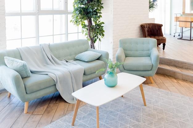 Modische, geräumige wohnung mit stilvollem design in den pastellfarben grün, grau und weiß mit großem fenster und dekorativen wänden. schlafzimmer und küche