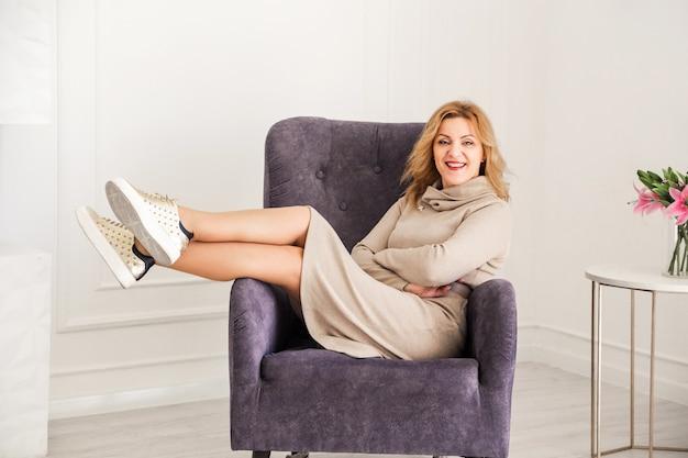 Modische geschäftsfrau, die kleid und turnschuhe trägt, die auf stuhl mit erhöhten beinen sitzen, lächelnd und kamera betrachten.