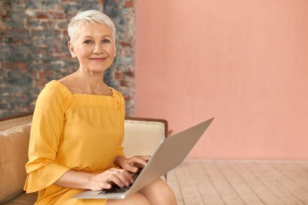 Modische geschäftsfrau mittleren alters, die e-mails überprüft, auf der couch mit tragbarem computer auf ihrem schoß sitzt, tastaturen verwendet und drahtlose hochgeschwindigkeits-internetverbindung zu hause verwendet. menschen, alter und technik