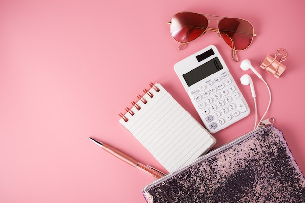 Modische glitzertasche mit notizblock, taschenrechner und sonnenbrille