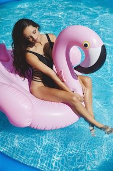 Modische, glückliche und lächelnde brünette vorbildliche frau mit einem perfekten sexy körper im stilvollen schwarzen bikini, der auf einem aufblasbaren rosa flamingo am swimmingpool im freien aufwirft