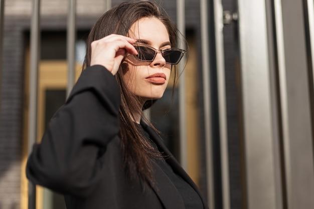 Modische hübsche junge attraktive frau in stilvoller, lässiger jugendkleidung richtet trendige sonnenbrillen in der nähe der vintage-metallwand im freien in der stadt auf. frisches porträt sexy mädchen in retro-kleidung auf der straße
