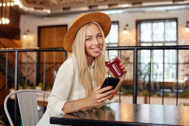 Modische hübsche junge langhaarige blonde frau mit schönen blauen augen, die mit charmantem lächeln schauen, smoothie mit stroh trinkend, während über restaurantinnenraum sitzen