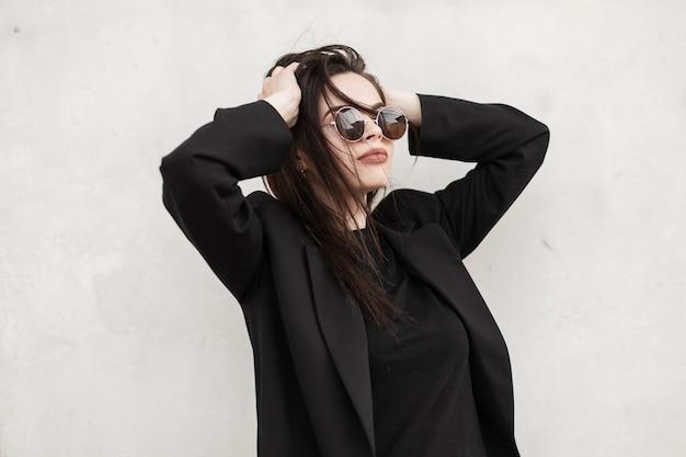Modische junge attraktive frau in stylischer, lässiger jugendkleidung in trendiger sonnenbrille glättet die frisur in der nähe der grauen vintage-wand im freien in der stadt. frisches porträt eines sexy mädchens auf der straße