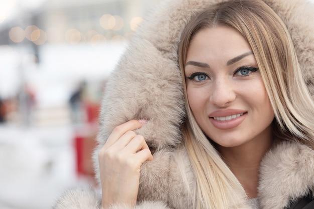 Modische junge blonde frau im modemantel in der stadt.