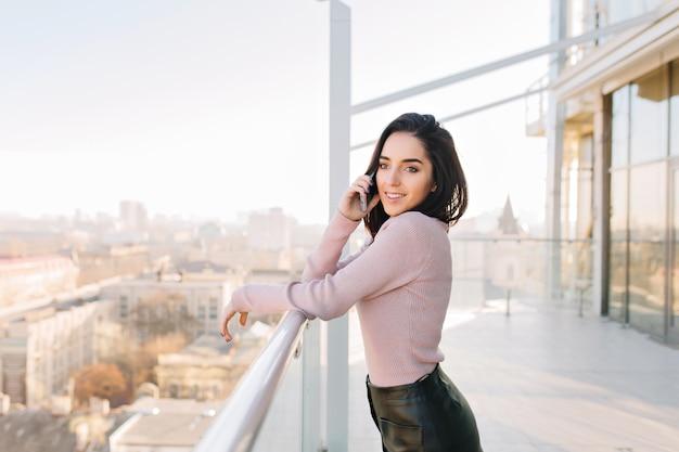 Modische junge brünette frau, die am telefon auf terrasse auf stadtansicht im sonnigen morgen spricht. erfolg, luxus-lifestyle, chillen, entspannen, freudige geschäftsfrau, lächeln zur seite.
