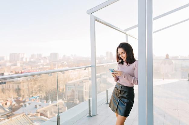 Modische junge brünette frau im schwarzen rock unter verwendung des telefons auf der terrasse auf stadtansicht.