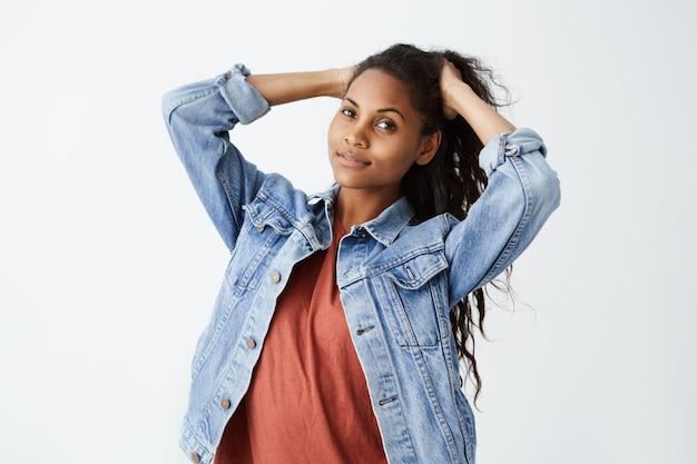 Modische junge dunkelhäutige frau, die jeansjacke und rotes lässiges t-shirt trägt, das ihr schönes dunkles gewelltes haar beim aufstellen bindet.