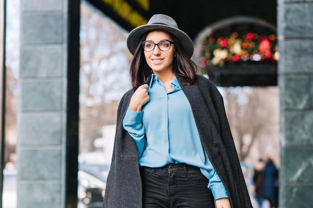 Modische junge frau des luxus stilvollen stadtporträts, die auf straße in der stadt zur weihnachtszeit geht. grauer hut, mantel, brünettes haar, schwarze brille, blaues hemd, fröhliche stimmung, geschäftsfrau.