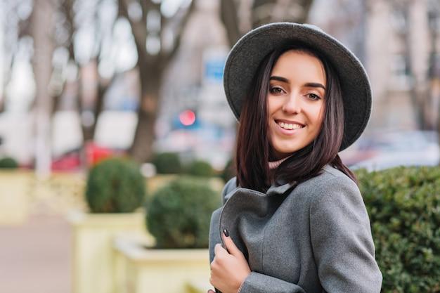 Modische junge frau des nahaufnahmeporträts im grauen hut, mantel, der auf straße im stadtpark geht. brünettes haar, lächelnd, fröhliche stimmung, eleganter blick.