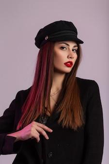 Modische junge frau des porträts mit braunem haar mit gesunder, sauberer haut mit schönen geschwollenen roten lippen in trendiger mütze in stilvoller schwarzer jacke im studio. modisches sexy mädchen-mode-modell im raum.