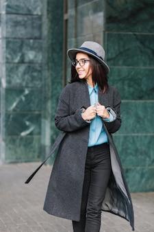 Modische junge frau des stilvollen stadtporträts, die im langen grauen mantel auf straße geht. hut tragen, schwarze brille, zur seite lächeln, wahre glückliche gefühle zeigen, junge geschäftsfrau.