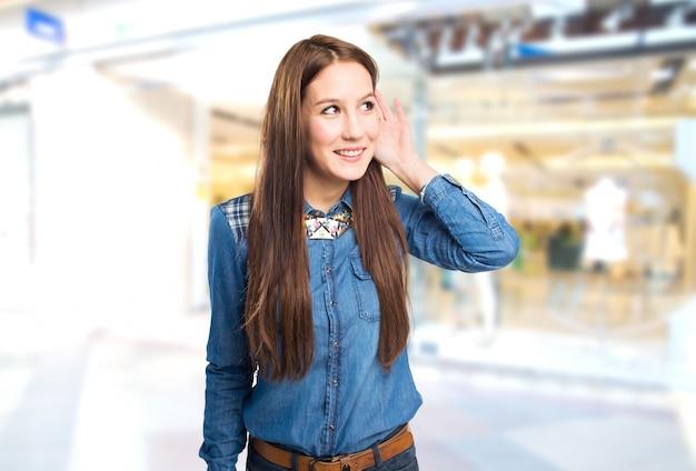 Modische junge frau die aufmerksamkeit mit ihrer hand auf ihrem ohr