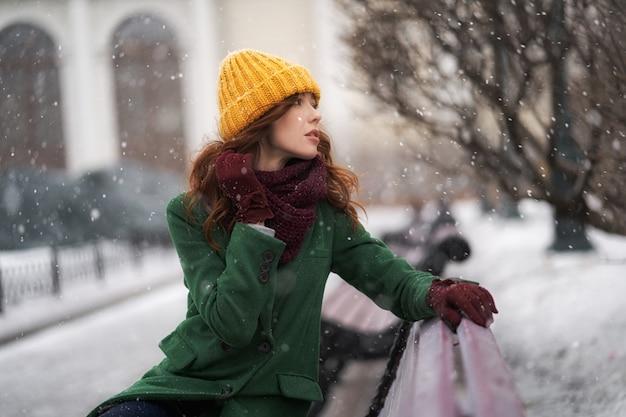 Modische junge frau, die draußen in einer stadtstraße aufwirft. winterporträt im freien, im schneefall