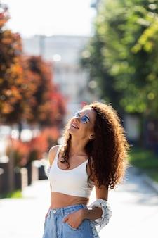 Modische junge frau, die draußen mit sonnenbrille aufwirft