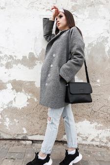 Modische junge frau im trendigen grauen mantel mit stilvollem bandana mit modischer schwarzer tasche liegt in der nähe der weißen vintage-wand in der straße. attraktives mädchen in lässiger frühlingskleidung, die in der stadt aufwirft. alltagslook.