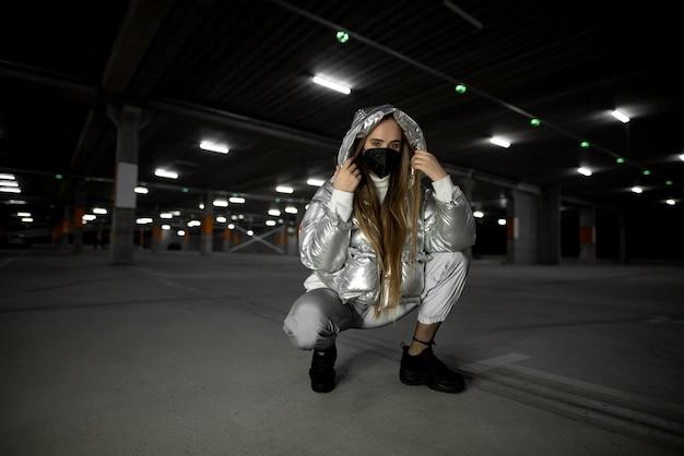 Modische junge frau in der maske am ungrundlosen parkplatz des einkaufszentrums. pandemie frau konzept