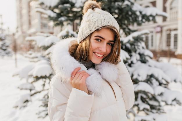 Modische junge frau in der weißen strickmütze, die freundlich auf der straße voll mit schnee lächelt. erstaunliche europäische frau, die winterzeit genießt