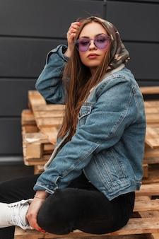 Modische junge frau in lila brille in stilvoller kleidung setzt militärkapuze auf den kopf. amerikanisches trendiges hipster-mädchen in jugendjeans freizeitkleidung posiert auf vintage-holzbrettern im freien sitzend