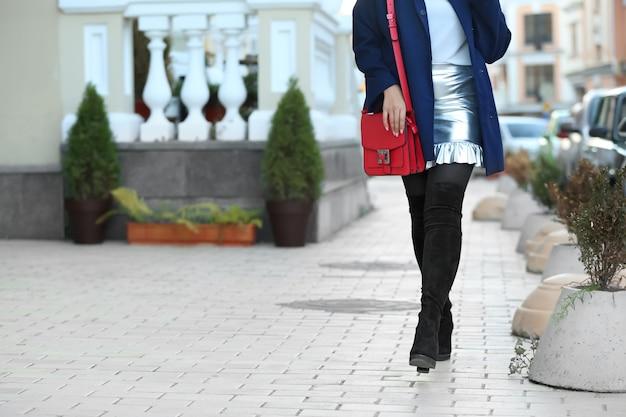 Modische junge frau in stilvollen stiefeln mit tasche im freien