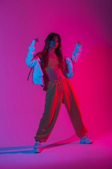 Modische junge frau in stilvoller sportbekleidung in schuhen, die im studio mit mehrfarbiger ultravioletter farbe posiert. schöne mädchentänzerin, die in einem raum mit leuchtend rosa neonlichtern tanzt. stil.