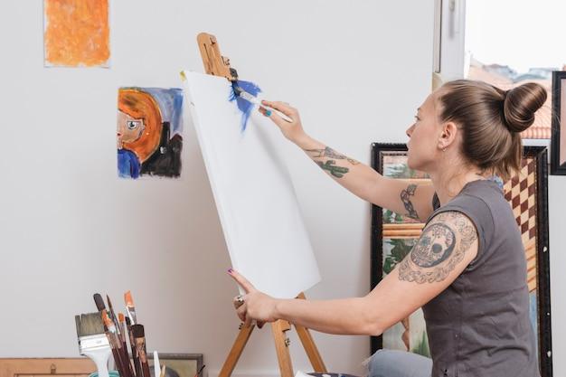 Modische junge frau mit den tätowierungen, die im blau malen