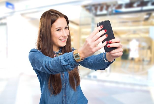 Modische junge frau mit einem smartphone ein bild zu machen