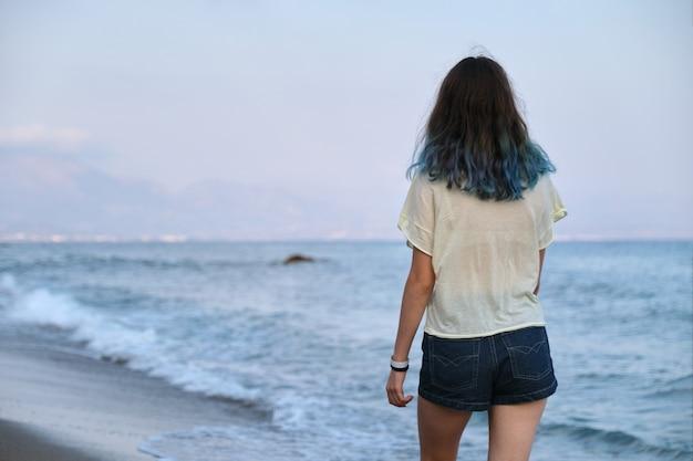 Modische junge frau mit gefärbten langen blauen haaren, die entlang der küste gehen. schönheit, mode, naturkonzept. rückansicht, sonnenuntergang auf see, kopierraum