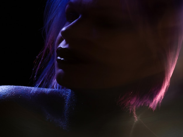Modische junge frau mit stilvollem glänzendem make-up des blauvioletten haares