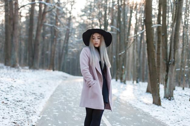 Modische junge fraublondine in einem stilvollen glamourösen mantel in einem schwarzen kleid in einem stilvollen schwarzen hut steht in einem verschneiten winterwald an einem sonnigen tag. attraktives mädchen auf einem spaziergang. moderne damenmode