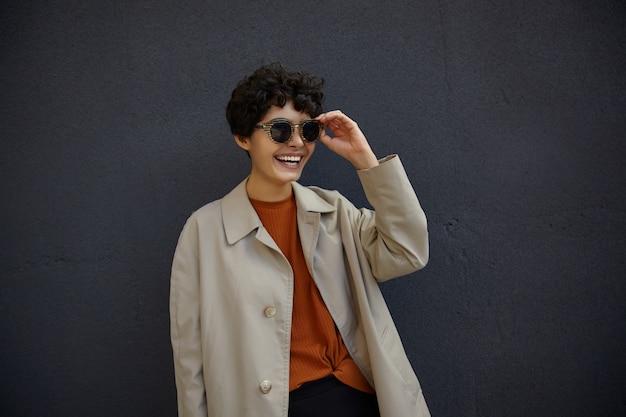Modische junge lockige frau mit kurzem haarschnitt, die trendiges outfit trägt, während sie draußen geht, über schwarzer stadtmauer aufwirft, hand auf ihrer sonnenbrille hält und fröhlich lächelt