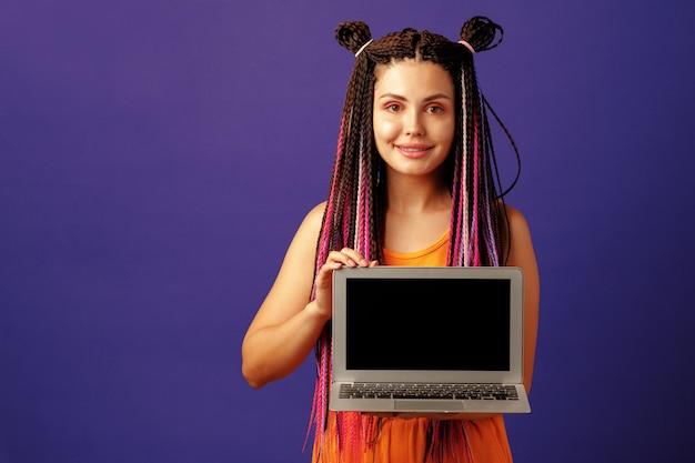 Modische junge studentin mit langen afro-zöpfen, die laptop gegen lila hintergrund halten
