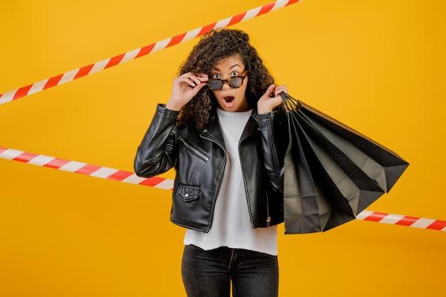 Modische junge tragende jacke der schwarzen frau mit den papiereinkaufstaschen lokalisiert über gelb mit signalband