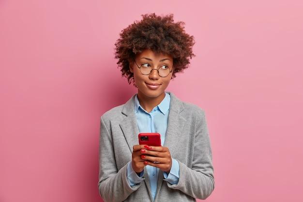 Modische junge unternehmerin in stilvollen formellen kleidern, hält handy, sendet nachrichten, chattet online, scrollt soziale netzwerke, liest artikel im internet