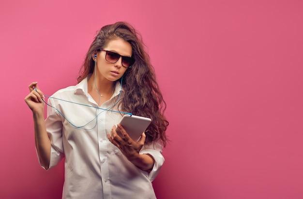 Modische kaukasische junge frau in einem weißen hemd in den gläsern mit kopfhörern, die eine weiße tablette in den händen auf einer rosa bunten wand halten.