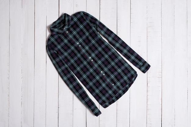 Modische klamotten. grünes kariertes hemd auf weißen bretterbodenplanken