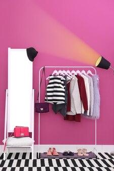 Modische kleidung, die am gestell am modernen ankleidezimmer hängt