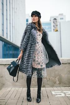 Modische lächelnde frau, die in der stadt im warmen pelzmantel, wintersaison, kaltes wetter, das tragen der schwarzen mütze, des kleides, der stiefel, des haltens der ledertasche, des straßenmodetrends geht