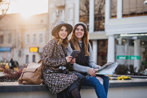 Modische lächelnde frauen, die im zentrum der stadt sitzen und helle gefühle an sonnigem tag in der stadt ausdrücken. viel spaß beim gemeinsamen reisen und beim versuch, den ort auf der karte zu finden.