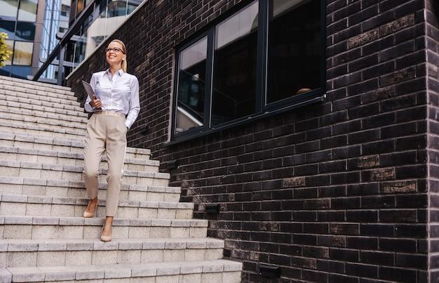 Modische lächelnde geschäftsfrau, die die treppe hinuntergeht, während tablette in ihren händen hält.