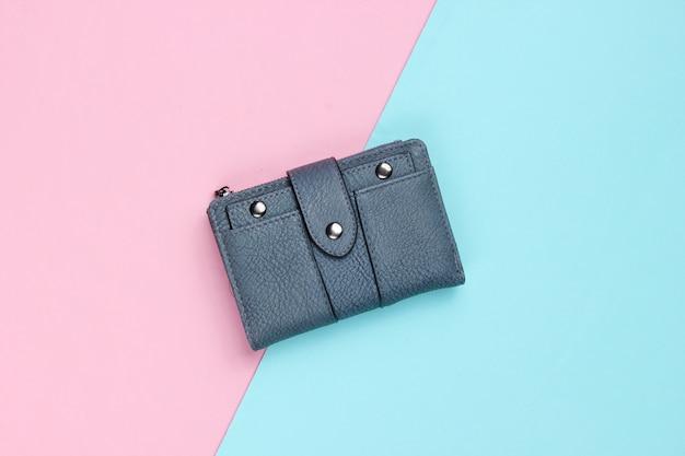 Modische lederbrieftasche auf einem blau-rosa pastell. draufsicht
