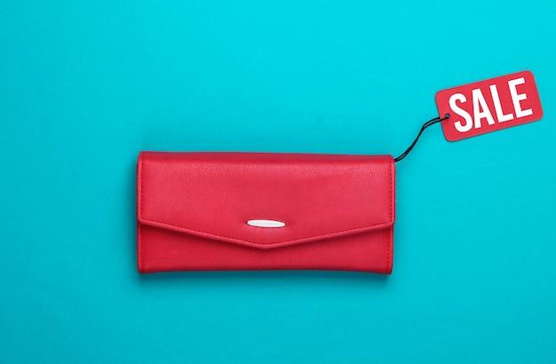 Modische lederbrieftasche mit rotem verkaufsetikett auf blau. rabatt. minimalismus