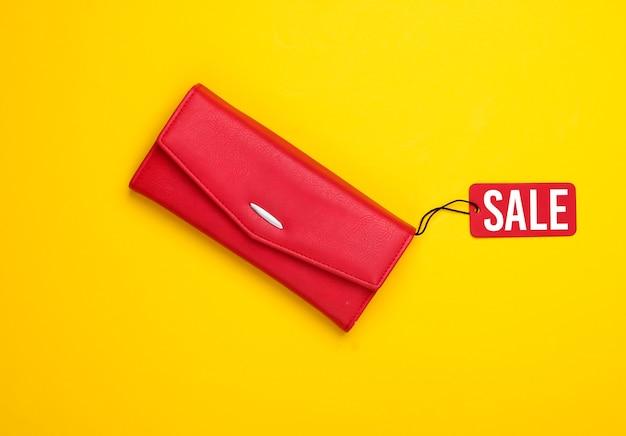 Modische lederbrieftasche mit rotem verkaufsetikett auf gelb. rabatt. einkaufen. minimalismus